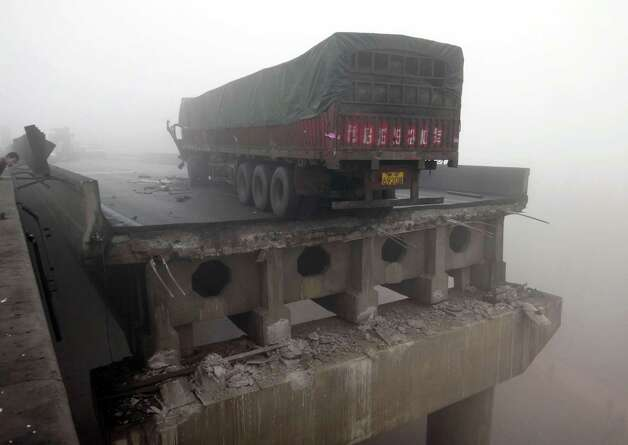 n this photo provided by China's Xinhua News Agency, a truck sits on the expressway bridge which partially collapsed due to an explosion in Mianchi County, Sanmenxia, central China's Henan Province, Friday, Feb. 1, 2013.  Fireworks for Lunar New Year celebrations exploded on a truck in central China, destroying part of an elevated highway Friday and sending vehicles plummeting 30 meters (about 100 feet) to the ground. (AP Photo/Xinhua, Xiao Meng)  Photo: AP