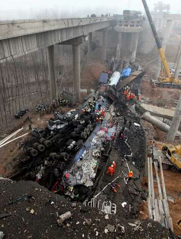 In this Feb. 1, 2013 photo provided by China's Xinhua News Agency, rescuers work at the accident site where an 80-meter (260 foot) section of an expressway bridge collapsed in Mianchi County, Sanmenxia, central China's Henan Province.   An elevated portion of highway in central China collapsed on Friday after a truck loaded with fireworks for Lunar New Year celebrations exploded, killing at least nine people and sending vehicles plummeting 30 meters (about 100 feet) to the ground. (AP Photo/Xinhua, Zhang Xiaoli) NO SALES Photo: AP