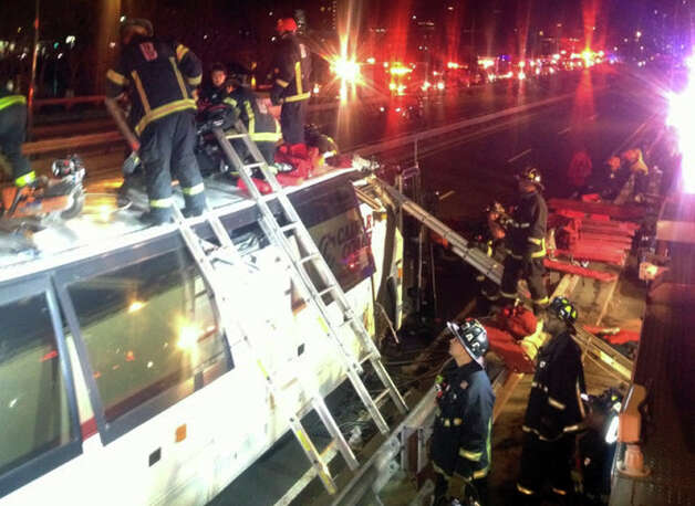 In this photo released by the Boston Fire Department via Twitter, firemen work to remove injured passengers from a bus that hit an bridge as it traveled along Soldiers Field Road in the Allston neighborhood of Boston Saturday night, Feb. 2, 2013. Officials said the bus carryinyg 42 people was traveling from Harvard University home to Pennsylvania when it struck the overpass. Photo: AP