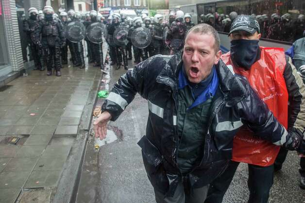 A steel worker from ArcelorMittal in Liege, Belgium, shouts during a protest near the Walloon Minister President's office in Namur, Belgium, Tuesday, Jan. 29, 2013. The world's leading steel and mining company ArcelorMittal announced Thursday it will close a coke plant and six production lines in Belgium, in a move that threatens 1,300 jobs. Photo: AP