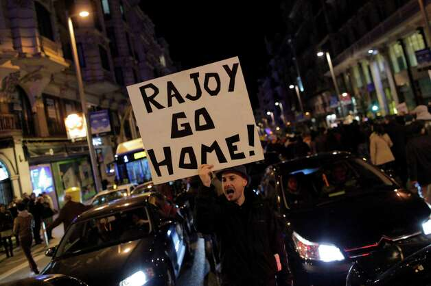 "Protestors shout slogans as they carry banners reading, ""Rajoy go home"" during a demonstration against corruption in Madrid, Spain, Saturday. Spain's governing Popular Party insists its financial accounts are totally legal and denies a newspaper report of regular under-the-table payments to leading members, including current Prime Minister Mariano Rajoy. The scandal first broke when after the National Court reported that former party treasurer Luis Barcenas amassed an unexplained euro 22 million ($30 million) in a Swiss bank account several years ago. In a statement Thursday Jan. 31, 2013, the party denied the existence of ""hidden accounts"" or ""the systematic payment to certain people of money other than their monthly wages"". Spain's top prosecutor says there is sufficient cause to investigate fresh allegations of irregular financing of Spain's governing Popular Party and that if necessary Prime Minister Mariano Rajoy would be called in for questioning. Photo: AP"