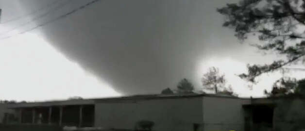 In this image made from video and released by WSB TV in Atlanta, a tornado moves through the town of Adairsville, Ga. on Wednesday, Jan 30, 2013. A fire chief says a storm that roared across northwest Georgia has left overturned vehicles on Interstate 75 northwest of Atlanta, and crews are responding to reports of people trapped in storm-damaged residential and commercial buildings. (AP Photo/WSB TV) Photo: AP