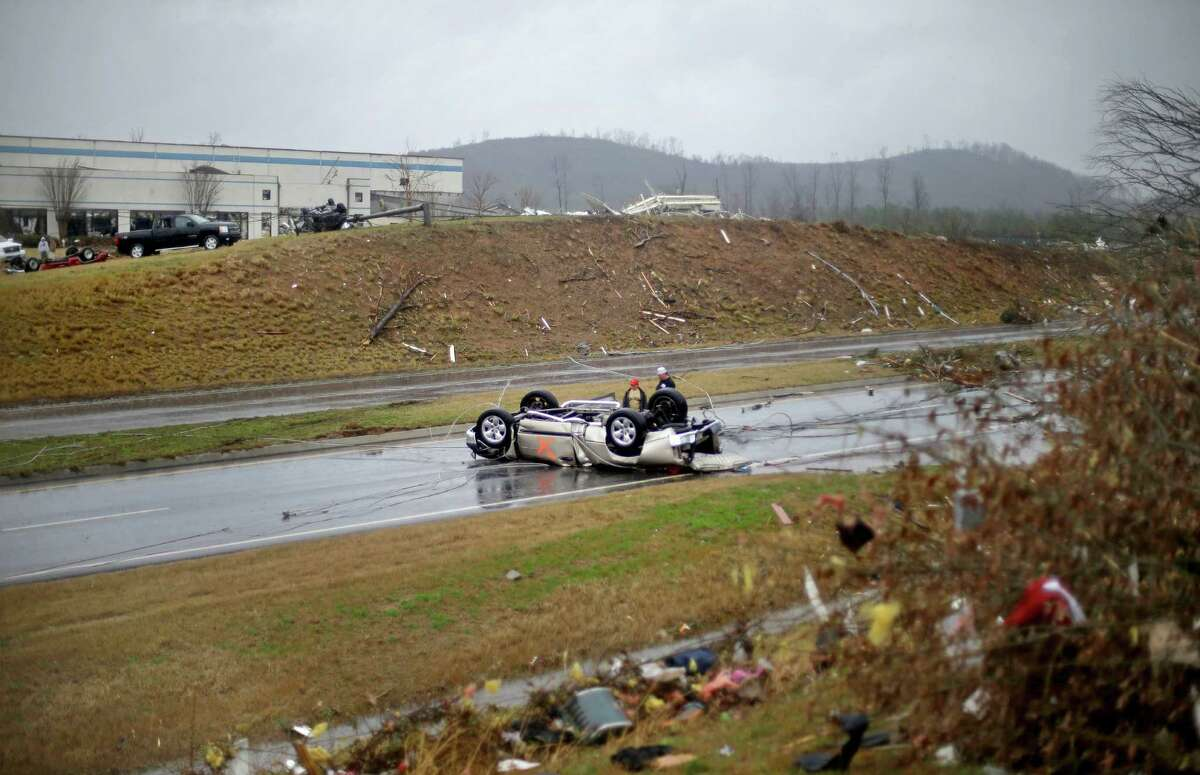 Tommy Stouffer, right, looks at his overturned car with his son Jonathan, 11, after a tornado picked it up from the parking lot where he was working across the street and dumped it in the middle of the road, Wednesday, Jan. 30, 2013, in Adairsville, Ga. A fierce storm system that roared across Georgia has left at least one person dead after it demolished buildings and flipped vehicles on Interstate 75 northwest of Atlanta.