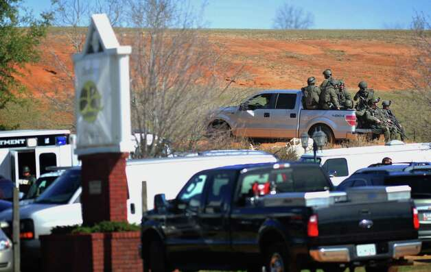 Law enforcement personnel in tactical gear ride a pickup to the scene of an ongoing hostage crisis on Friday below the site where Tuesday's school bus shooting suspect is barricaded in a bunker holding a five-year-old boy captive. More than three days after authorities said a gunman shot a school bus driver dead, grabbed a kindergartner and slipped into an underground bunker, the man showed no signs Friday of turning himself over to police. Photo: AP