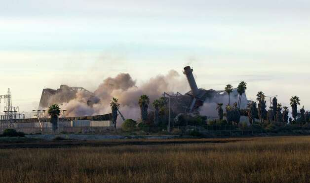 The South Bay Power Plant collapses after imploding, Saturday in Chula Vista, Calif. In a matter of minutes, a hulking power plant that loomed over San Diego Bay since the late 1950s was demolished Saturday, to make way for a city park. The implosion, which had been months in the planning, turned the mighty structure into a heap of concrete and twisted steel. (AP Photo/U-T San Diego, Nelvin C. Cepeda)  Photo: AP