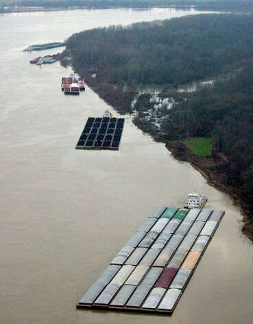 Five barges sit to the east of the Vicksburg Tallulah Regional Airport at dusk waiting for traffic to open along the Mississippi River near Vicksburg, Miss. on Monday.  A barge carrying thousands of gallons of oil struck a railroad bridge and began leaking before dawn Sunday. The accident forced the closure of a 16-mile stretch of the lower Mississippi, a major inland corridor for vessels carrying oil, fuel, grain and other goods. (AP Photo/The Vicksburg Evening Post, Melanie Thortis ) Photo: AP