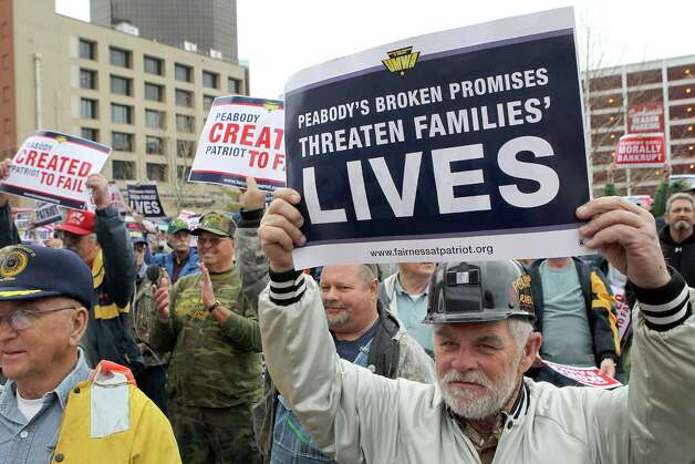 Retired Peabody miner Dale Walcher, 68, of Litchfield, Ill. right, holds up a sign during a rally in front of the federal courthouse before marching four blocks to Peabody Energy headquarters in St. Louis on Tuesday, Jan. 29, 2013.  Ten union mine workers have been arrested following a protest outside Peabody Energy headquarters. Workers and retirees were seeking to draw attention to what they consider poor treatment from Patriot Coal Corp., a company spun off from Peabody five years ago. A hearing on Patriot's bankruptcy was Tuesday in St. Louis. Mine workers said the protest was a bid to save health care and pension benefits that could be stripped away in Chapter 11 proceedings. (AP Photo/St. Louis Post-Dispatch, Stephanie S. Cordle)  Photo: AP
