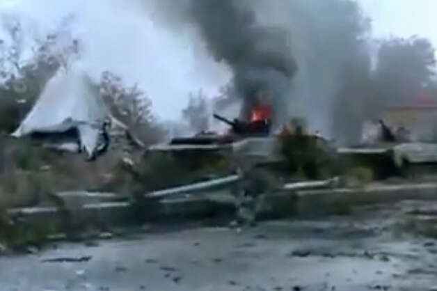 This image taken from video obtained from the Ugarit News, which has been authenticated based on its contents and other AP reporting, shows a military tank that caught on fire in front of the government intelligence complex in Deir el-Zour, Syria, on Tuesday. Syrian rebels stormed a government intelligence complex in the oil-rich east of the country on Tuesday, freeing at least 11 people held in a prison at the facility, activists said. Photo: AP