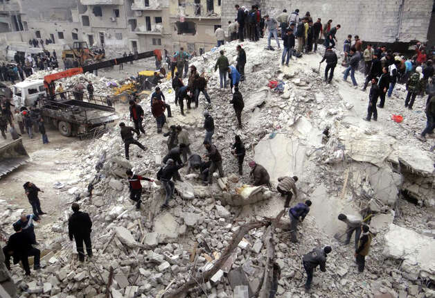 This citizen journalism image provided by Aleppo Media Center, AMC, which has been authenticated based on its contents and other AP reporting, shows people searching  through the debris of destroyed buildings after airstrikes hit the neighborhood of Eastern Ansari, in Aleppo, Syria, Sunday. The Britain-based activist group Syrian Observatory for Human Rights, which opposes the regime, said government troops bombarded a building in Aleppo's rebel-held neighborhood of Eastern Ansari that killed over 10 people, including at least five children. Photo: AP