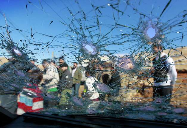 Lebanese civilians are seen through a bullet riddled car window, in Arsal, a Sunni Muslim town eastern Lebanon near the Syrian border, Saturday. At least three Lebanese soldiers were killed and five others were wounded in clashes Friday between the army and gunmen in the northeast near the Syrian border, a police official and the state-run news agency said. Photo: AP