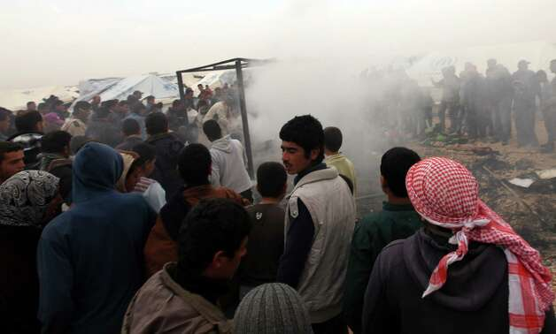 Syrian refugees extinguish fire after it caught on a tent at Zaatari Syrian refugees camp, in Mafraq, near the Syrian border, Jordan, Monday. A refugee tent caught on fire, and the family who lives in it was evacuated by the refugees. Photo: AP