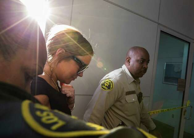 Lindsay Lohan is escorted by Los Angeles County Sheriffs, Wednesday, Jan. 30, 2013, as she arrives in court for a pretrial hearing in a case filed over the actress' June car crash in Los Angeles. Lohan faces three misdemeanor charges, and a return to jail, if convicted in the case or if a judge finds she violated her probation. Photo: AP