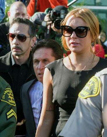 Lindsay Lohan, right, her new attorney Mark Heller, background center, leave a Los Angeles court, Wednesday. Photo: AP