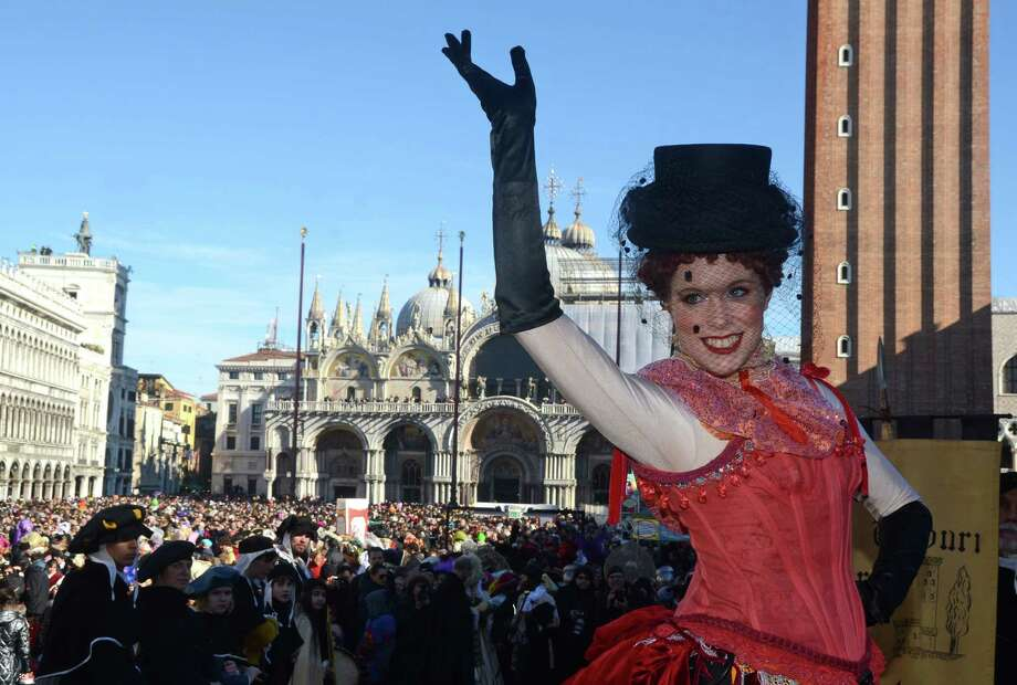 "Marta Finotto, a student at Venice's University, dressed in a traditional costume, salutes after descending from the bell tower into St. Mark square, during the ""Angel's flight"", one of the highlights of the opening day of the Venice Carnival, in Venice, Italy, Sunday. Photo: Luigi Costantini, AP / AP"