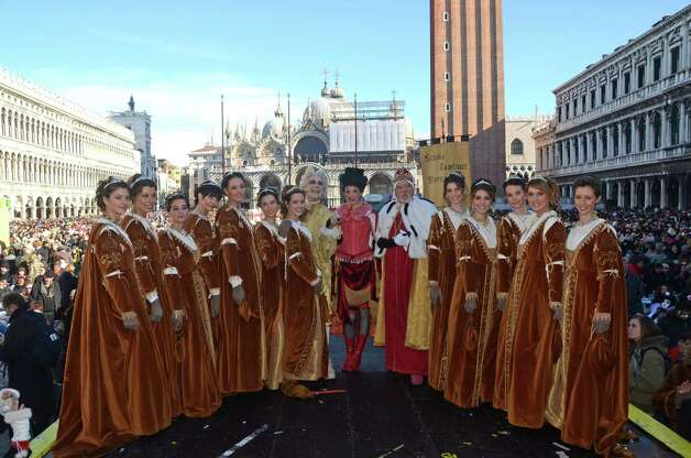 "Marta Finotto, center, a student at Venice's University, dressed in a traditional costume, poses with other traditional masks after descending from the bell tower into St. Mark square, during the ""Angel's flight"", one of the highlights of the opening day of the Venice Carnival, in Venice, Italy, Sunday. Photo: Luigi Costantini, AP / AP"