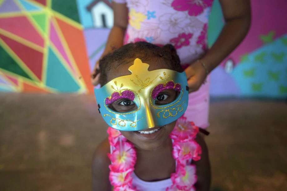 A young girl stands still as an older girl secures her decorative mask during a pre-carnival celebration in Rio de Janeiro, Brazil, Friday.  Photo: AP