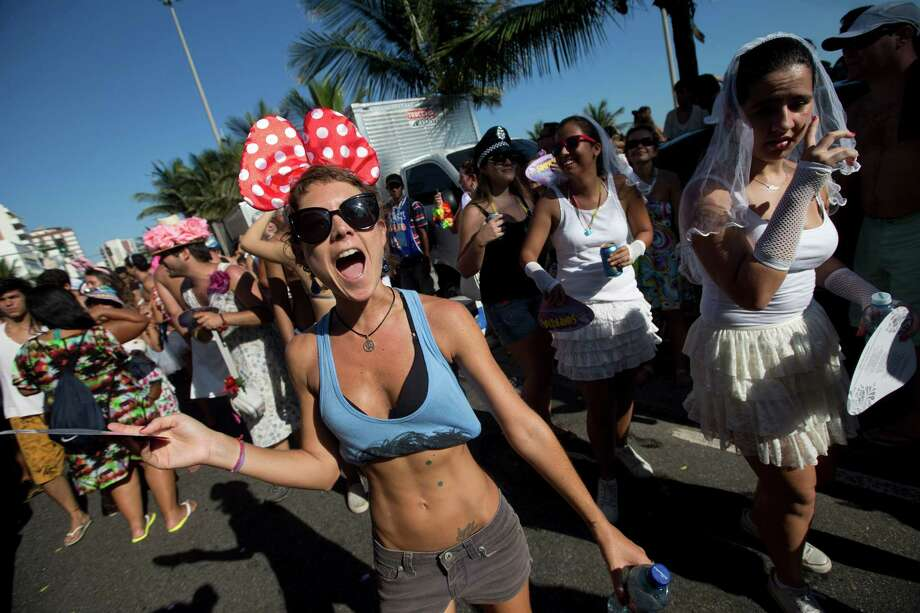"A woman wearing a Minnie Mouse like-bow shouts outs in revelry at the Simpatia e Quase Amor or ""Kindness is almost love,"" block party, a pre-Carnival celebration in Rio de Janeiro, Brazil, Saturday. According to Rio's tourism office, Rio's street Carnival this year will consist of 492 block parties, attended by an estimated five million Carnival enthusiasts. Photo: AP"