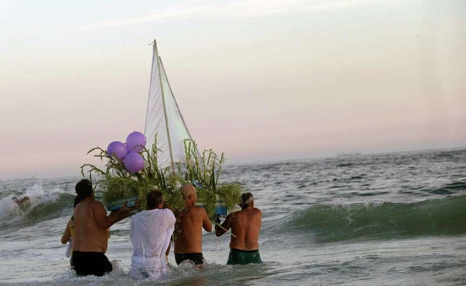 "Simpatia e Quase Amor or ""Kindness is almost love,"" block party members and faithful carry a boat filled with flowers as an offering to the sea goddess Yemanja, during a pre-Carnival celebration in Rio de Janeiro, Brazil, Saturday. Worshippers honor the deity, offering flowers and launching boats, large and small, into the ocean showing their gratitude for her blessings bestowed upon them. Photo: AP"