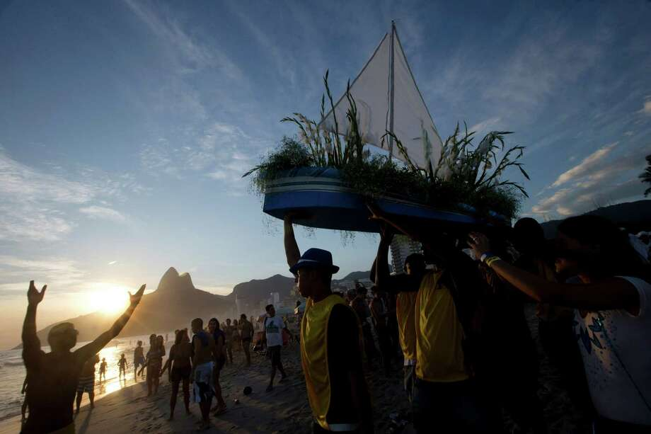 "Simpatia e Quase Amor or ""Kindness is almost love,"" block party members and faithful carry a boat filled with flowers as an offering to the sea goddess,Yemanja, during a pre-Carnival celebration in Rio de Janeiro, Brazil, Saturday.  Photo: AP"