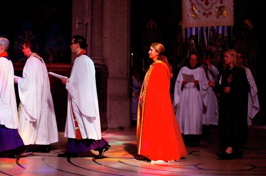 The Reverend Becca Stevens, in red, makes her way down the aisle of the Grace Cathedral on Sunday morning Feb. 3 The clergy wore red and gold vestments in support of the San Francisco 49ers as they enter the Super Bowl today. Photo: James Tensuan, The Chronicle / ONLINE_YES