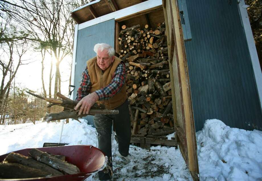 David Coles loads some firewood from his wood shed outside his Shelton home. Coles has been heating with home with wood that he splits and stacks himself for the last thirty years. Photo: Brian A. Pounds / Connecticut Post