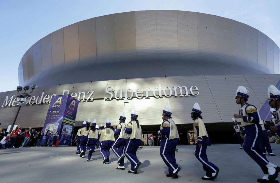 Members of the Warren Easton High School marching band of New Orleans perform outside of the Superdo