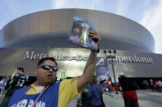 Jose Rodriguez, of Madera, Calif., sells programs outside of the Superdome. Photo: Elaine Thompson, Associated Press / AP