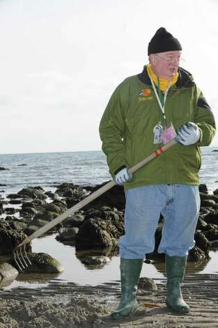 Bill Cameron, of Shellfish Commission, show people how to clam at the beach near Innis Arden Cottage Sunday, Feb. 3, 2013. Innis Arden Cottage at Greenwich Point celebrates its opening following Superstorm SandyTown Conservation Director Denise Savageau speaks of the historic flooding including water levels and storm surge throughout the open house. Additionally, members of the Friends of Greenwich Point and the Greenwich Point Conservancy give an update on repair and restoration activities. This event is hosted by the Friends of Greenwich Point, the Greenwich Point Conservancy the Shellfish Commission, and the Town of Greenwich Conservation Commission. Photo: Helen Neafsey / Greenwich Time
