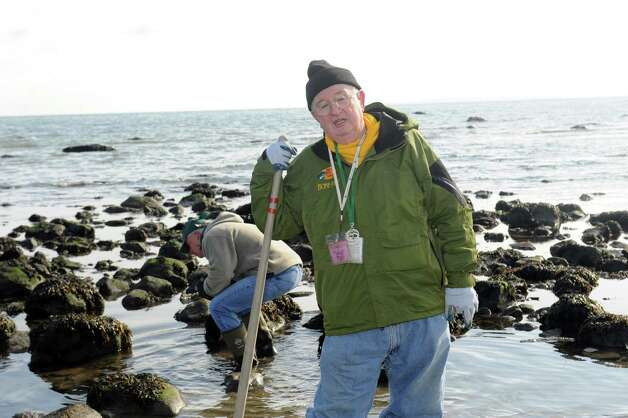 Bill Cameron, of Shellfish Commission, shows people how to clam at the beach near Innis Arden Cottage Sunday, Feb. 3, 2013. Innis Arden Cottage at Greenwich Point celebrates its opening following Superstorm Sandy.Town Conservation Director Denise Savageau speaks of the historic flooding including water levels and storm surge throughout the open house. Additionally, members of the Friends of Greenwich Point and the Greenwich Point Conservancy give an update on repair and restoration activities. This event is hosted by the Friends of Greenwich Point, the Greenwich Point Conservancy the Shellfish Commission, and the Town of Greenwich Conservation Commission. Photo: Helen Neafsey / Greenwich Time