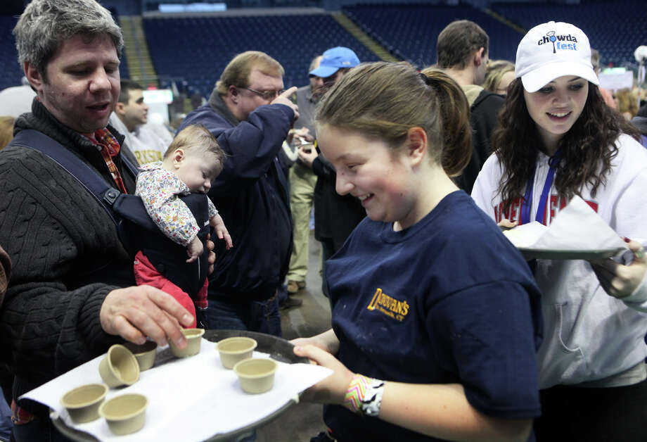 Nicole Festa, 11, center, and Lauren Dufresne, right, serve chowder from Donovan's, in South Norwalk,   during Chowda Fest at Webster Bank Arena in Bridgeport , Conn., on Sunday, February 3, 2013.  The Unitarian Church in Westport sponsors the event, which raises money for the Connecticut Food Bank. Photo: BK Angeletti, B.K. Angeletti / Connecticut Post freelance B.K. Angeletti