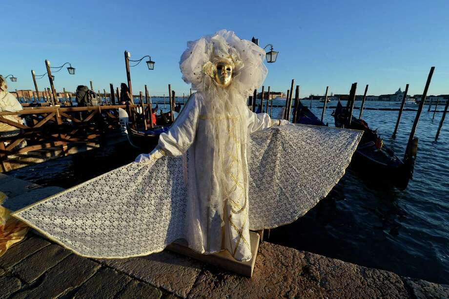 "Costumed revellers pose near St Mark's square during the carnival on Sunday in Venice. The 2013 edition of the Venice carnival is untitled "" Live in Colour"" and runs from January 26 to February 12. AFP PHOTO / VINCENZO PINTO Photo: VINCENZO PINTO, Getty / 2013 AFP"