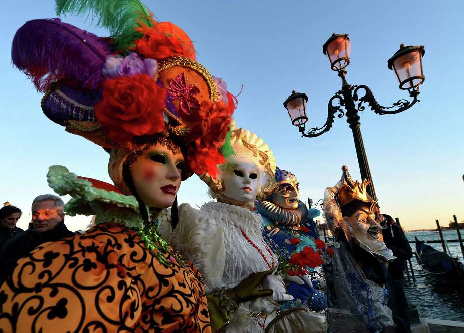 "Costumed revellers pose near St Mark's square during the carnival on Monday in Venice. The 2013 edition of the Venice carnival is untitled "" Live in Colour"" and runs from January 26 to February 12. AFP PHOTO / VINCENZO PINTO Photo: VINCENZO PINTO, Getty / 2013 AFP"