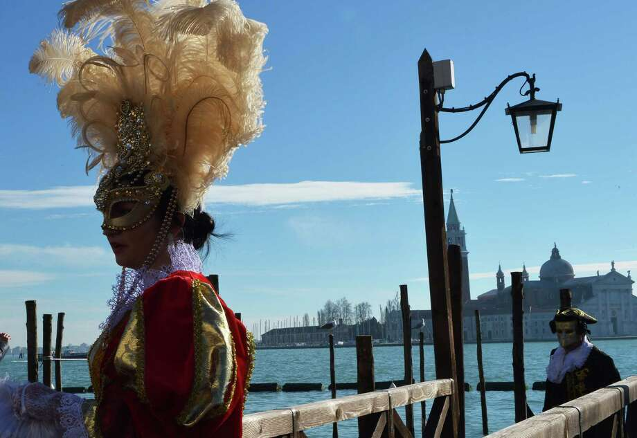 """Costumed revellers arrive at St Mark's square during the carnival on Monday in Venice. The 2013 edition of the Venice carnival is untitled """" Live in Colour"""" and runs from January 26 to February 12. AFP PHOTO / VINCENZO PINTO Photo: VINCENZO PINTO, Getty / 2013 AFP"""
