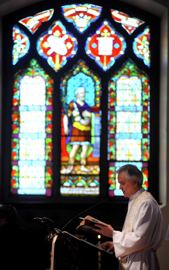 Framed by stained glass windows, St. Mark's Episcopal Church Rector Michael Chalk reads from scripture Sunday, Feb. 3, 2013, during the rededication ceremony at the historic downtown church following the completion of a $15 million renovation. Photo: Robin Jerstad, For The Express-News