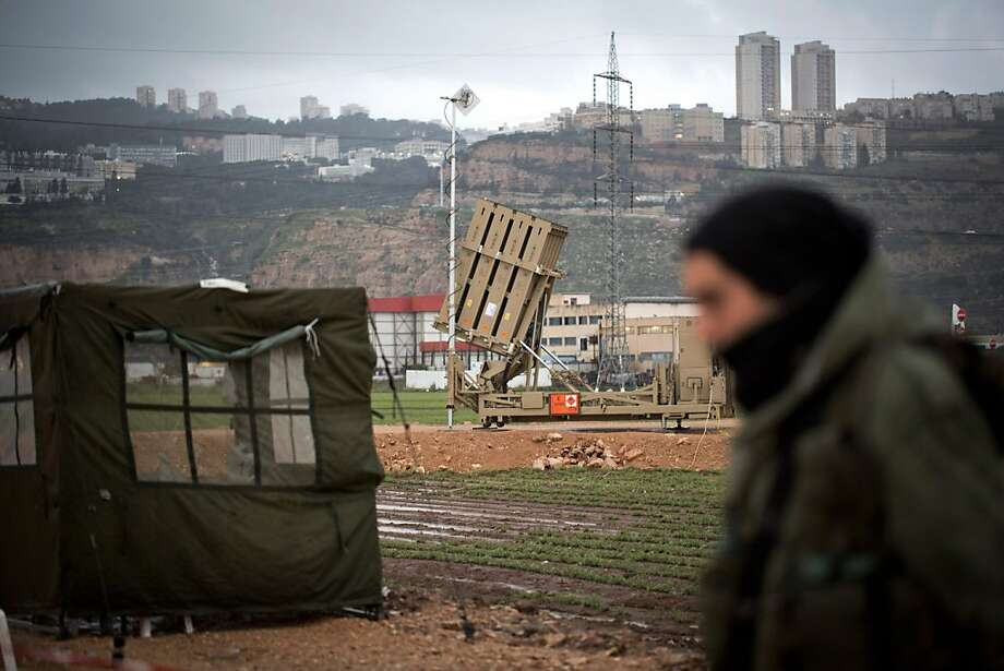 An Israeli soldier walks by a short-range missile defense system near Haifa. Israel's departing defense minister indirectly confirmed an attack on Syria. Photo: Getty Images