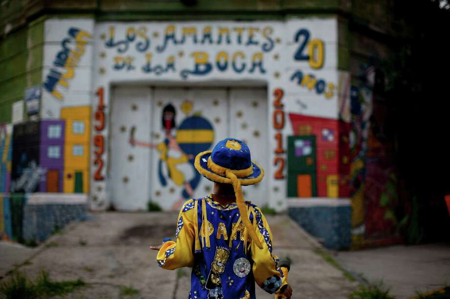 "Damian Carballo, a member of the murga ""Los amantes de La Boca,"" walks at the La Boca neighborhood before participating in carnival celebrations in Buenos Aires, Argentina, Saturday. Photo: AP"