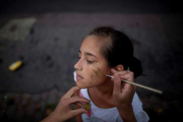 "Sol Basualdo, a member of the murga ""Los amantes de La Boca,"" has her makeup done in preparation for carnival celebrations in Buenos Aires, Argentina, Saturday. Photo: AP"