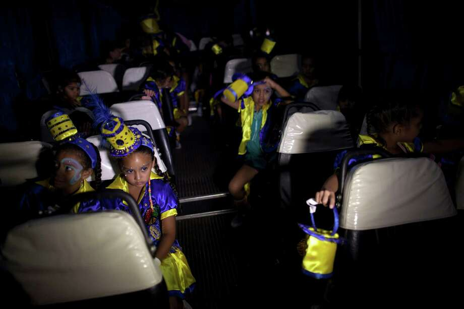 "Member of the murga ""Los amantes de La Boca"" wait inside a bus before heading to carnival celebrations in Buenos Aires, Argentina, Saturday. Photo: AP"