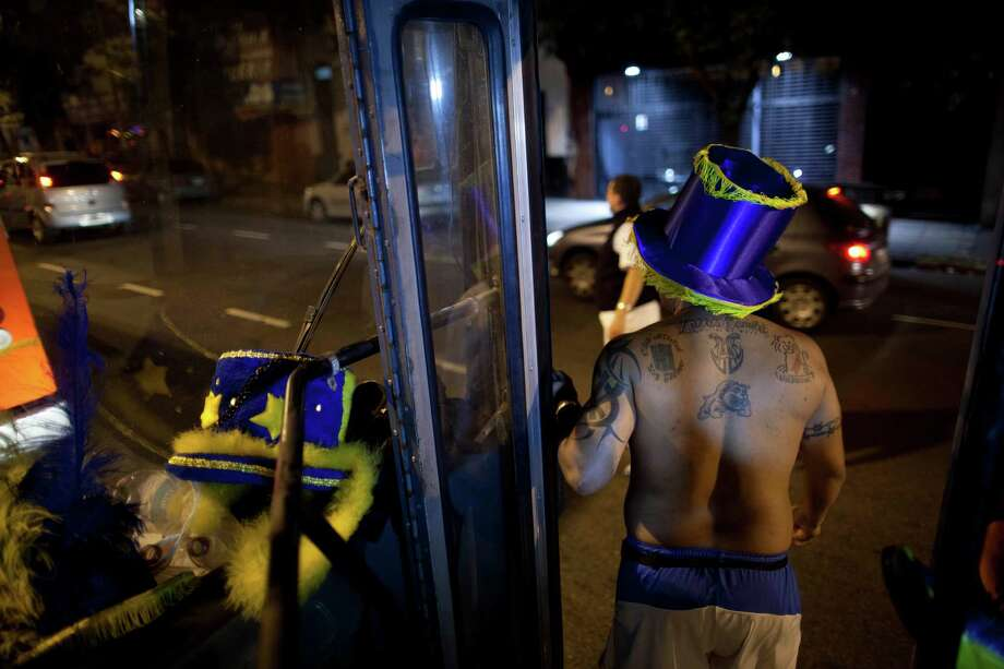 "A member of the murga ""Los amantes de La Boca"" stands on bus as he heads to carnival celebrations in Buenos Aires, Argentina, Saturday. Photo: AP"