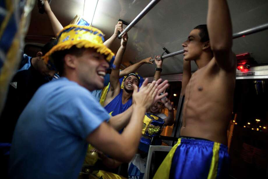 "Members of the murga ""Los amantes de La Boca"" have fun on a bus as they head to carnival celebrations in Buenos Aires, Argentina, Saturday. Photo: AP"