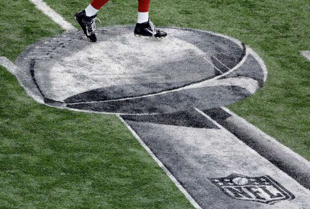 A San Francisco 49ers play runs past an NFL logo before the start of the NFL Super Bowl XLVII football game against the Baltimore Ravens Sunday, Feb. 3, 2013, in New Orleans. (AP Photo/Charlie Riedel) Photo: Charlie Riedel, Associated Press / AP