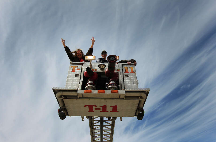 San Antonio firefighter Sean Wiatrek (center) takes exuberant civilian employee Jean Magargee (left) and Heidi Heridia (right) on a ride in an aerial platform during a civilian employee appreciation event at the San Antonio Fire Academy on Thursday, Jan. 31, 2013. The employees had an opportunity to see how firefighters worked a fire and took rides in fire trucks including a nearly 90-feet ride in the air in one of the department's aerial platform trucks. Photo: Kin Man Hui, San Antonio Express-News / © 2012 San Antonio Express-News