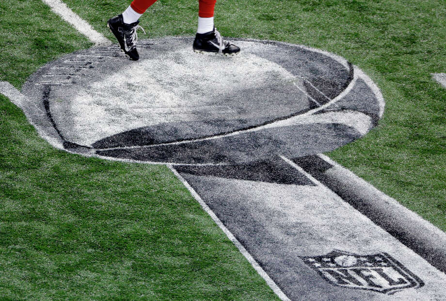 A San Francisco 49ers play runs past an NFL logo before the start of the Super bowl. Photo: Charlie Riedel