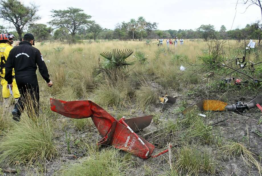 Workers inspect the site of a helicopter crash that killed a politician near Asuncion, Paraguay. Photo: ABC/Roque Gonzalez, Associated Press