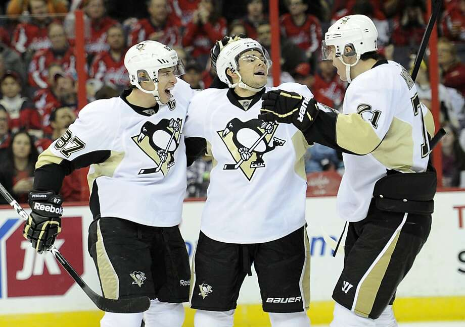 Chris Kunitz (center), who scored a hat trick, celebrates a second-period goal for the Penguins. Photo: Nick Wass, Associated Press