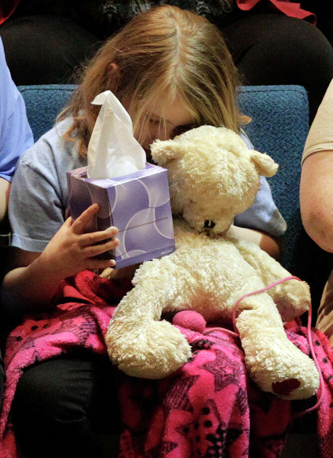 "Lauren Higginson, a student on  Charles ""Chuck"" Poland's bus, hugs her teddy bear during the ceremony to honor Poland at the Ozark Civic Center on Sunday, Feb. 3, 2013, in Ozark, Ala. (AP Photo/Butch Dill) Photo: Butch Dill, Associated Press / FR111446 AP"
