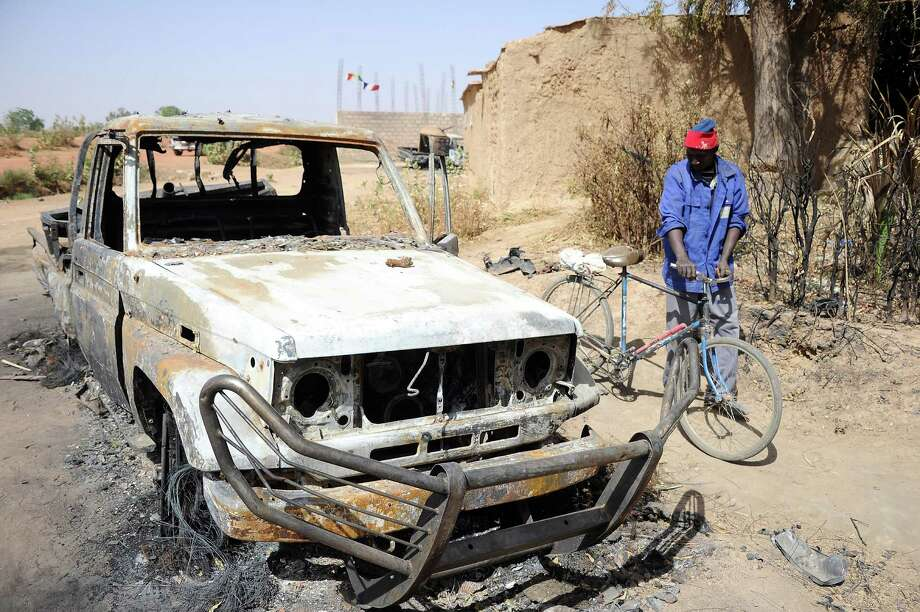 A man stands next to a bicycle past a burnt-out wreck of a vehicle, allegedly used by Islamists, following a major air strike, on February 3, 2013 in Diabaly. France said it carried out major air strikes on February 3, 2013 near Kidal, the last bastion of armed extremists chased from Mali's desert north in a lightning French-led offensive, after a whirlwind visit by President Francois Hollande. An army spokesman said 30 warplanes had bombed training and logistics centres run by Islamist extremists overnight in the Tessalit area north of Kidal, where French troops took the airport Wednesday and have been working to secure the town itself. AFP PHOTO / PASCAL GUYOTPASCAL GUYOT/AFP/Getty Images Photo: PASCAL GUYOT, AFP/Getty Images / AFP