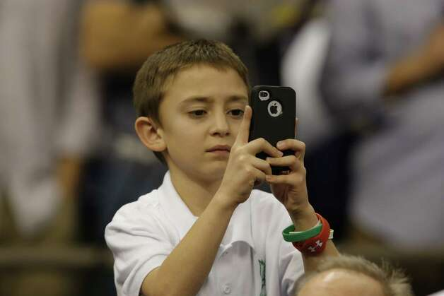 A Student from Sandy Hook Elementary School Choir takes photos before taking the field to sing America The Beautiful with Jennifer Hudson before the start of Superbowl XLVII between the San Francisco 49ers and the Baltimore Ravens at the Mercedes-Benz Superdome on Sunday February 3, 2013 in New Orleans, La. Photo: Brant Ward, The Chronicle / Connecticut Post contributed