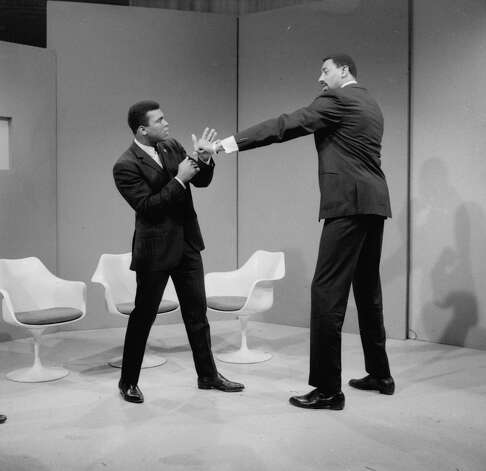 Basketball star Wilt Chamberlain extends a long left in the direction of world heavyweight champion Muhammad Ali as they met at an ABC television studio in New York, March 10, 1967.  Chamberlain stands 7 feet, 1 inch tall, and Ali is 6 feet, 2 inches tall.  Chamberlain's reach is over 90 inches, Ali's is 79 inches.  Their proposed fight, in all seriousness, never came off. Photo: AP / 1967 AP