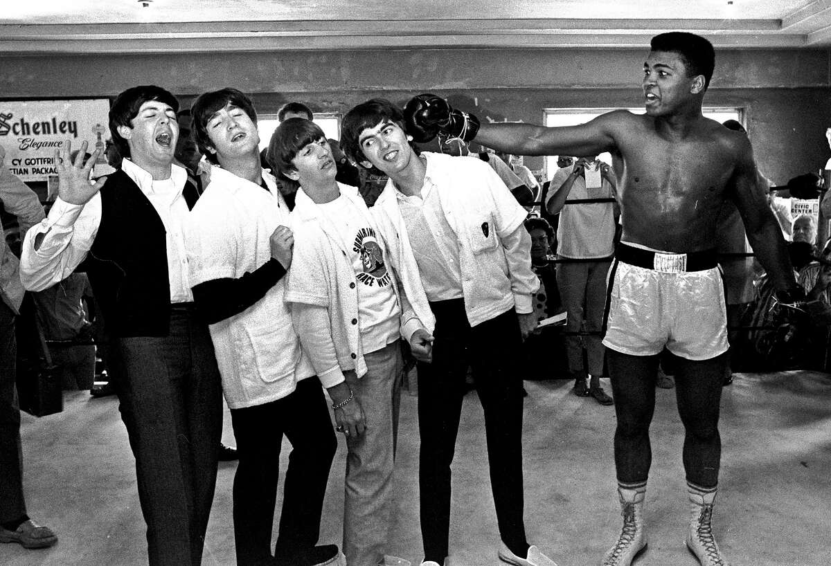 The Beatles, from left, Paul McCartney, John Lennon, Ringo Starr, and George Harrison, take a fake blow from Cassius Clay, who later changed his name to Muhammad Ali, while visiting the heavyweight contender at his training camp in Miami Beach, Fla.